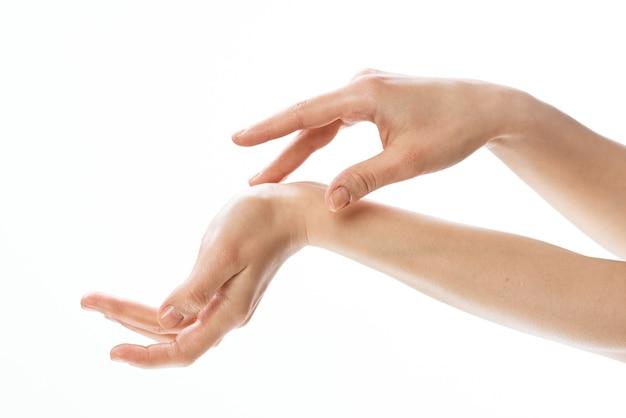女性の手のスキンケアクローズアップ化粧品明るい背景。高品質の写真
