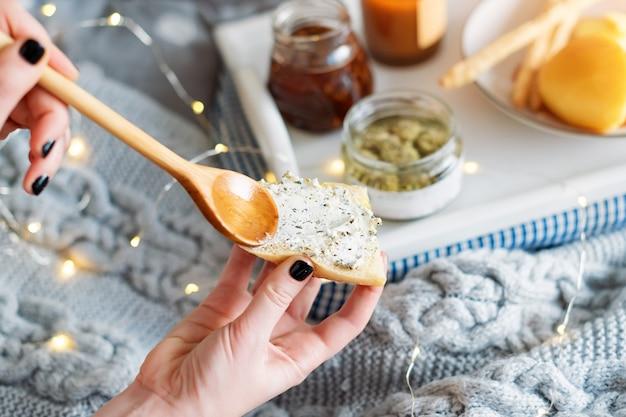 Женские руки, мажущие сливочный сыр на свежий хлеб