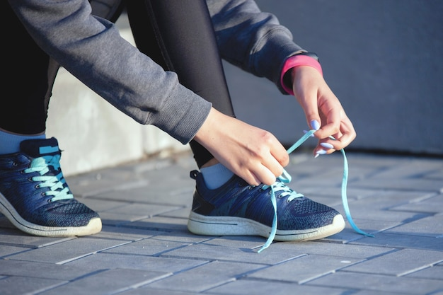 Female hands in sportswear tie shoe laces on sneakers on the stairs after a warm-up in the city