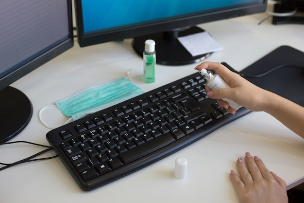 Женские руки спрей дезинфицирующее средство спрей на клавиатуре компьютера