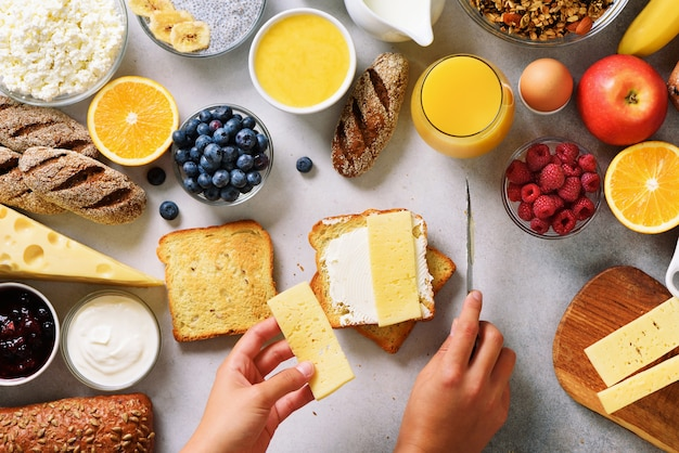 Female hands spreading butter on bread. woman cooking breakfast. healthy breakfast ingredients, food frame.