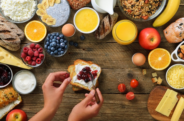 Female hands spreading butter and jam on bread. healthy breakfast ingredients, food frame. granola, nuts, fruits, berries, milk, yogurt, juice, cheese.