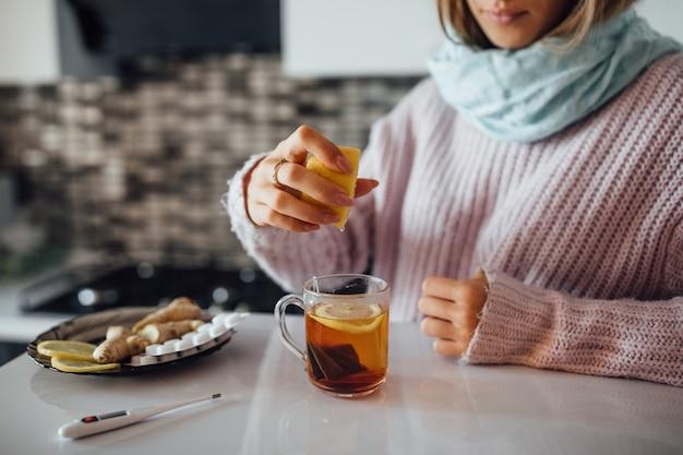 彼女のお茶にレモンを絞る女性の手。