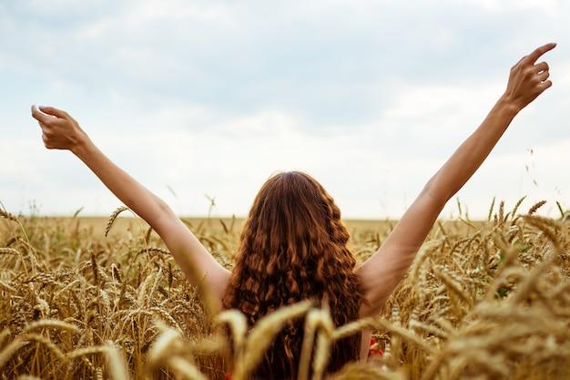 밀밭에서 여성의 손을 튀어 나와 행복 한 젊은 여자는 익은 황금 밀밭에서 무료입니다.