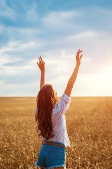 여성의 손이 밀밭에서 튀어나와 행복한 젊은 여성이 익은 황금빛 밀밭에서 자유롭습니다.