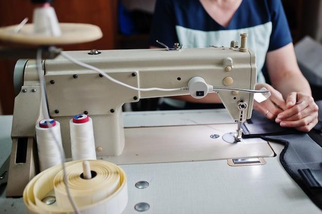 Женские руки сшивают ткань на профессиональной производственной машине на рабочем месте. швейный процесс.