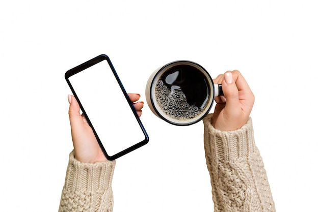 Female hands in sweater touch screen mobile phone with cup of coffee.