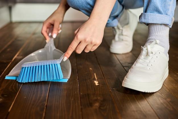 여성 손 브러시와 쓰레받기로 먼지를 쓸고 빗자루를 들고 바닥을 쓸고 쓰레받기에 먼지를 모으고 있습니다. 쓰레기 청소. 가정 개념. 쓰레기 청소. 파란색 브러시에 집중