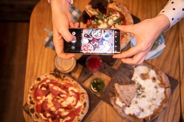 女性の手は、レストランでおいしいピザと一緒にスマートフォンのテーブルで写真を撮ります。上面図