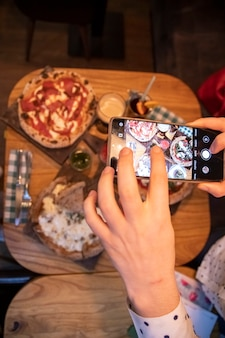 Female hands takes pictures on a smartphone table with a delicious pizza in a restaurant. top view
