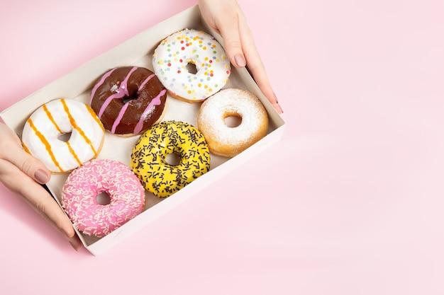 파스텔 핑크 표면에 도넛 상자에서 뿌리와 다채로운 둥근 유약 도넛을 복용하는 여성 손