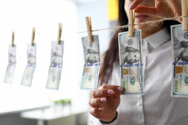 돈 세탁 개념으로 옷 라인에서 달러 지폐를 복용하는 여성 손