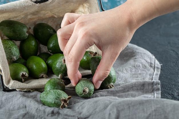 バスケットからフェイジョアの果実を取り出す女性の手。