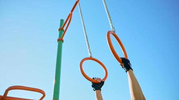 Женские руки берут гимнастические кольца на спортивной площадке