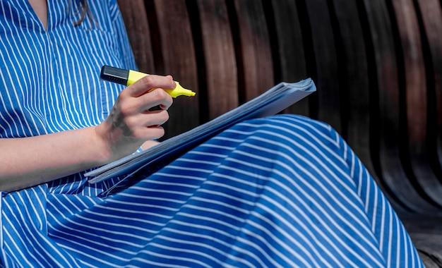 메모를 하는 여성의 손은 강의 계획서가 있는 공원의 벤치에 앉아 있거나 형광펜이 있는 책을 닫습니다.