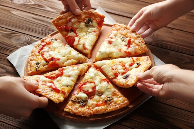 Female hands taking pizza slices on wooden table