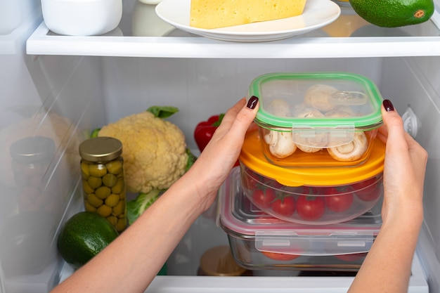 Female hands taking storage box with food from a fridge close up