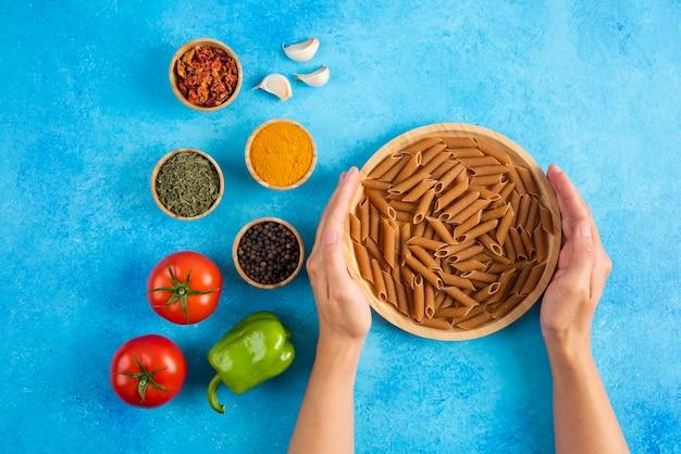 Mani femminili che prendono tavola di legno piena di pasta cruda. e ingredienti freschi sulla superficie blu.
