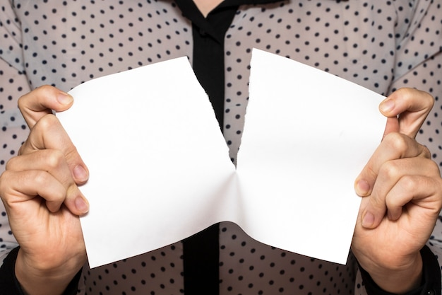Female hands tearing a sheet of paper
