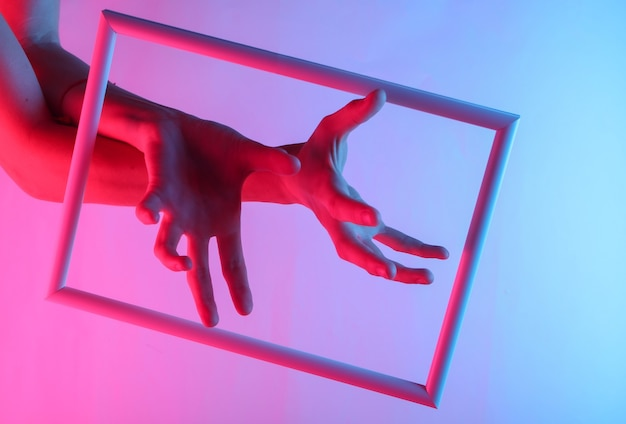 Female hands through a soaring frame with neon holographic light