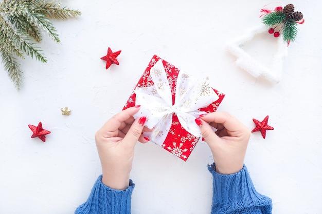 女性の手がクリスマスプレゼントに弓を結ぶ
