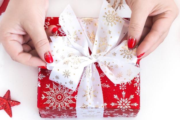 Женские руки завязывают бант на красной подарочной коробке.