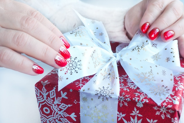 女性の手は赤いギフトボックスに弓を結びます。