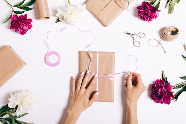 Female hands tie a ribbon on gift for a holiday on white table