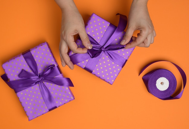Female hands tie a silk bow on a gift box, top view