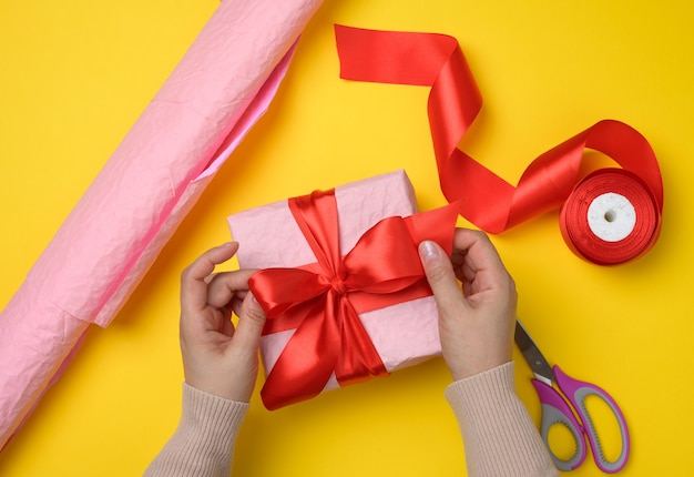 Female hands tie a silk ribbon on a wrapped box in pink paper. yellow background, top view