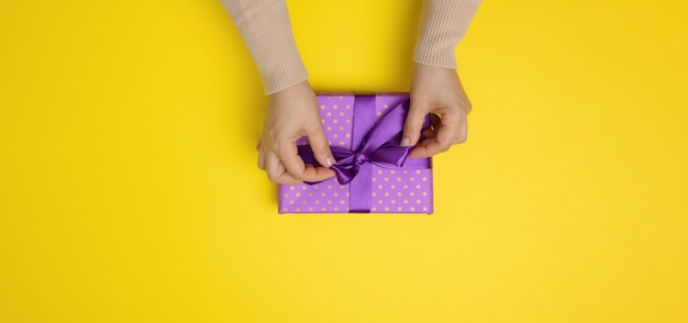 Female hands tie a silk ribbon on a wrapped box in purple paper. yellow background, top view