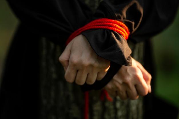 Женские руки связаны красной веревкой. жертва находится в лесу у дерева. преступность и агрессия. крупный план. низкий ключ.