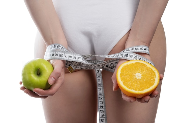 Female hands tied with measuring tape hold fruit