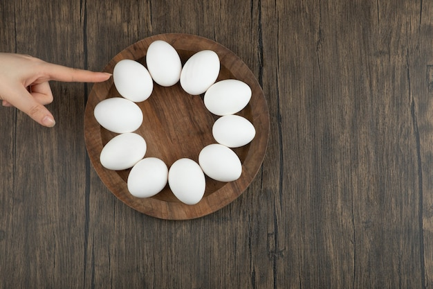 Female hands touching wooden board with raw eggs on wooden surface.