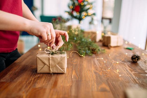 Женские руки связывают подарочную коробку праздничного ремесла с еловой веткой на деревянном столе