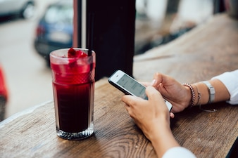 Female hands typing a message on mobile phone, sitting for the table with fruit cocktail