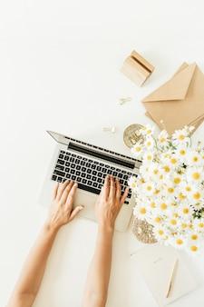 Женские руки, набрав состав. рабочий стол домашнего офиса с ноутбуком, букет цветов ромашки и блокнот на белом