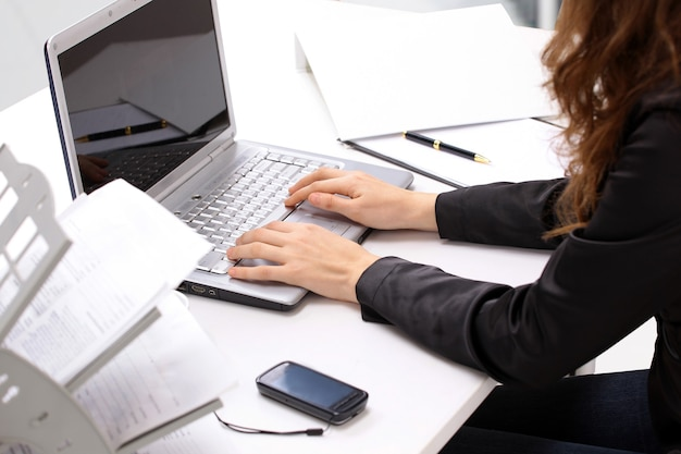 Female hands typing on a keyboard and holding mouse