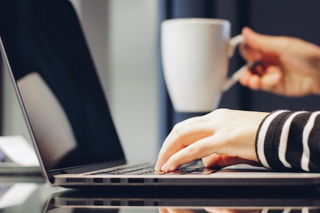 Female hands typing on keyboard of laptop while holding cup of coffee, working at home concept