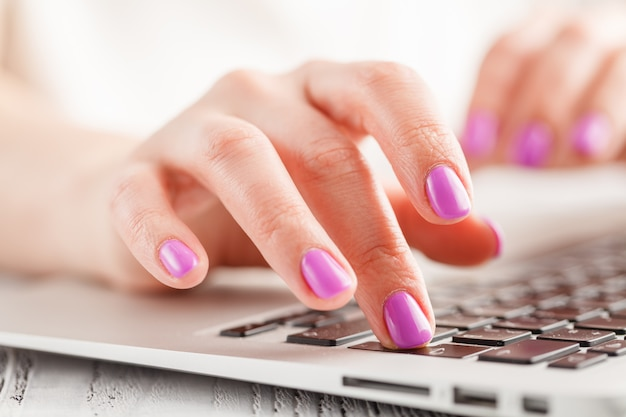 Female hands typing on laptop, on bright wall