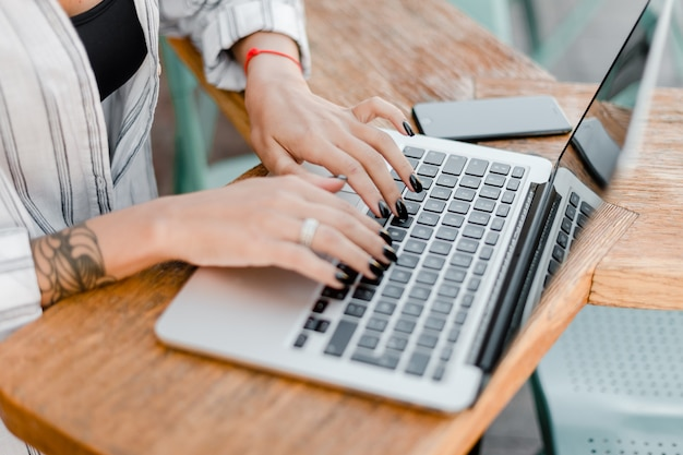 Female hands typing on laptop keyboard in the cafe