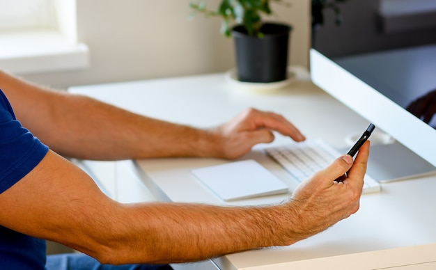 Female hands typing on laptop keyboard at the office, at home, phone in hand