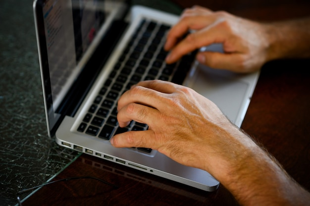 Female hands typing on laptop keyboard at the office, at home