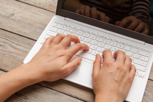 Female hands typing on a laptop keyboard top view