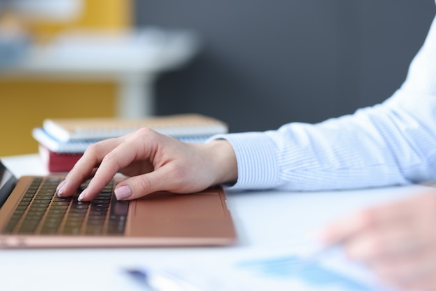Female hands typing on laptop keyboard at workplace