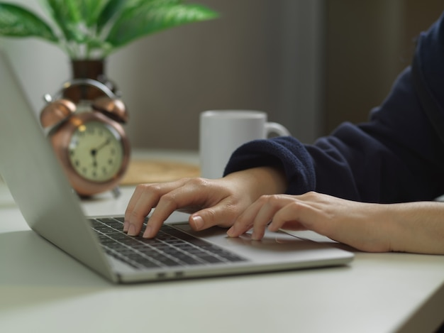 Female hands typing on laptop keyboard on worktable decorated with plant vase and clock