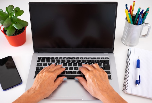 Женские руки, набрав на портативном компьютере. пустой экран. белый рабочий стол