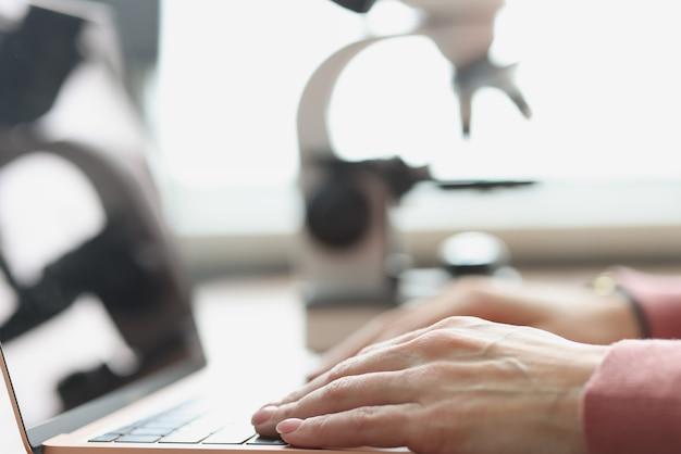 ノートパソコンのキーボードで入力する女性の手リモートワークと教育の概念