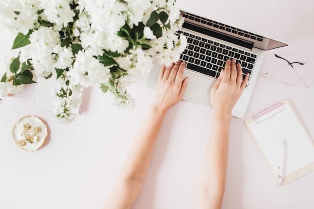 ノートパソコンで入力する女性の手。ピンクのテーブルにコンピューター、花束、文房具を備えたオフィスデスクワークスペース
