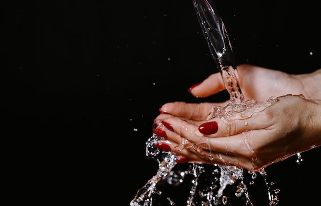 어두운 배경에서 흐르는 물 아래 여성 손